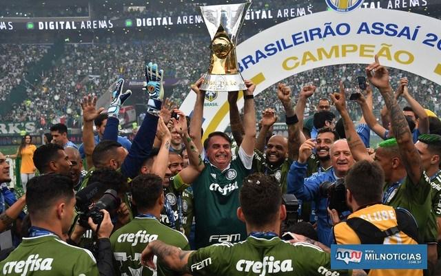 O presidente eleito, Jair Bolsonaro, ergue a taça do Campeonato Brasileiro com jogadores do Palmeiras — Foto: Nelson Almeida/AFP