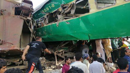 Socorristas paquistaneses e moradores se reúnem em volta dos destroços de trens que se chocaram no Paquistão na quinta-feira (11) — Foto: STR / AFP Photo.