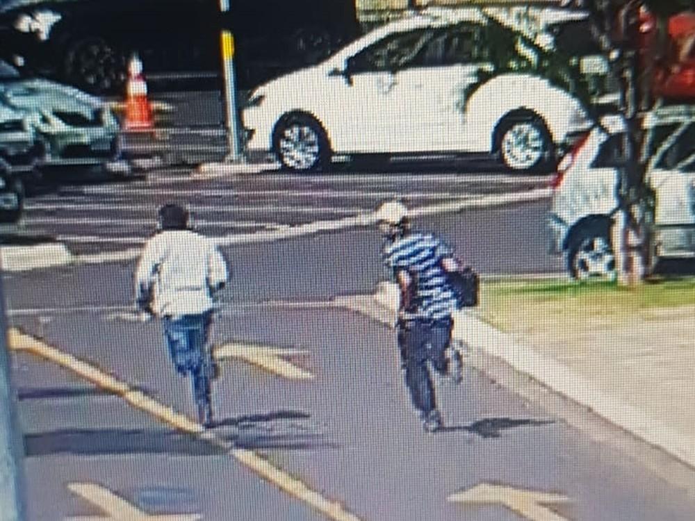 Suspeitos fugiram correndo pelo estacionamento em Araçatuba — Foto: Reprodução/Câmera de segurança.