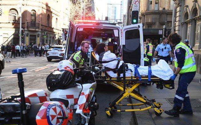 Mulher é levada para um hospital em Sydney, na Austrália, depois de ser esfaqueada nesta terça-feira (13) por um homem que tentou atingir várias pessoas no centro da cidade. — Foto: Dean Lewins/AAP Image via AP.