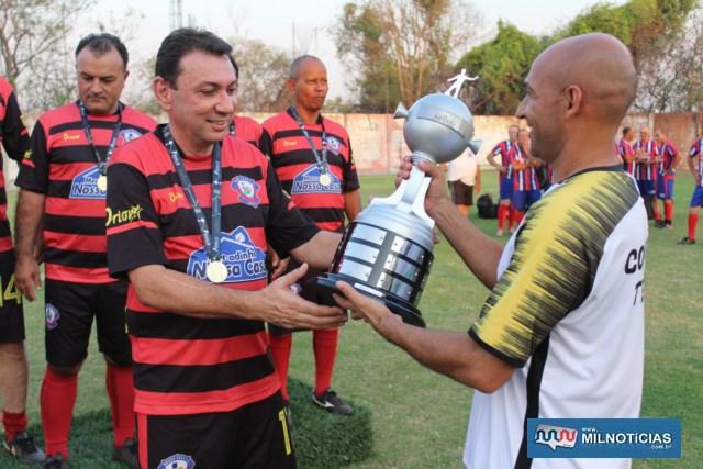 Basílio (dir.), entrega troféu de campeão ao capitão Júnior Suman, do Amigos do Tiziu. Foto: MANOEL MESSIAS/Agência