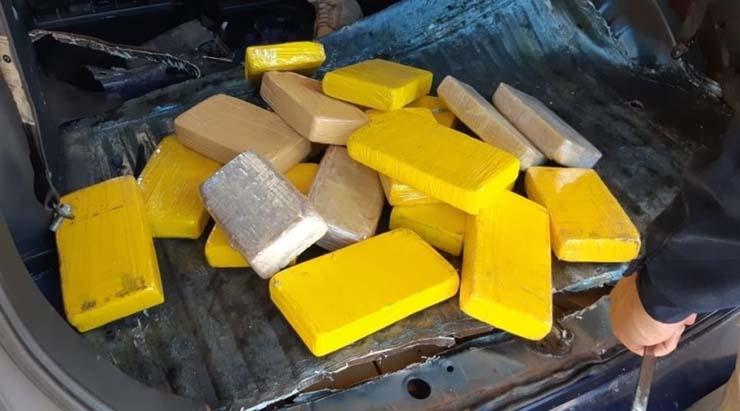 Tabletes com pasta base e cloridrato de cocaína que totalizaram 71 quilos da droga que foi encontrada em fundo falso de minivan de casal de paraguaios — Foto: PRF/Divulgação.