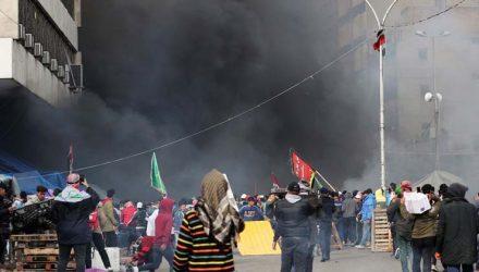 Manifestantes são vistos entre a fumaça subindo de tendas em chamas enquanto forças de segurança iraquianas atacam na Praça Tahrir durante protestos contra o governo em Bagdá — Foto: Thaier al-Sudani/Reuters.