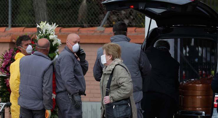 Agentes funerários carregam o caixão com vítima de Covid-19, no cemitério em Leganes, na Espanha, na terça-feira (24) — Foto: Manu Fernandez / AP.