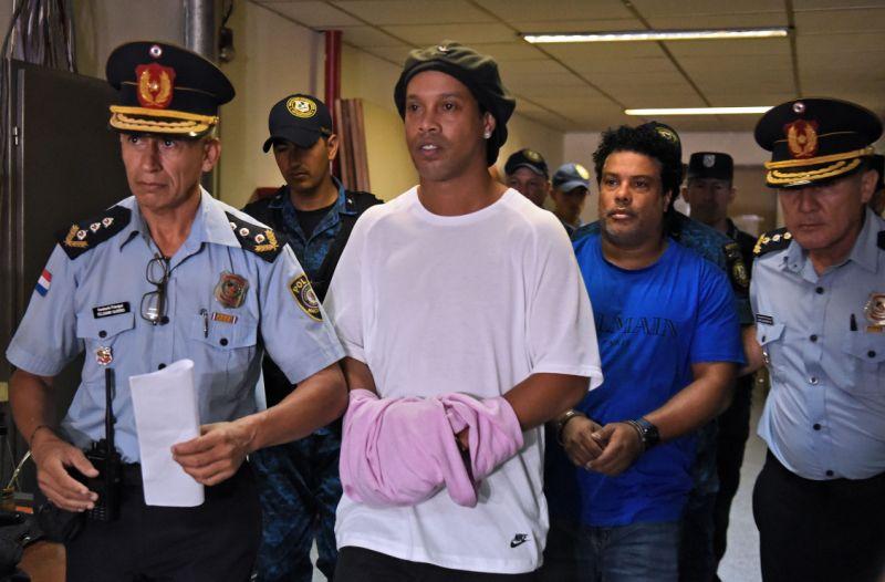 Ronaldinho e o irmão chegam algemados para audiência. Foto: NORBERTO DUARTE/AFP via Getty Images
