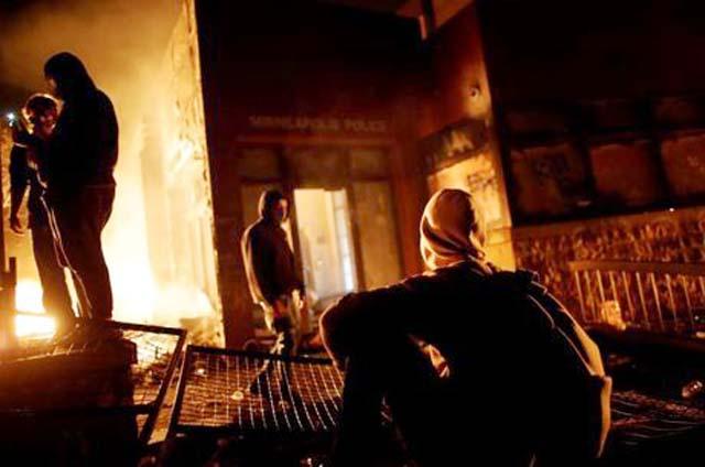 Manifestantes observam a entrada da delegacia incendiada em Minneapolis. REUTERS / Carlos Barria