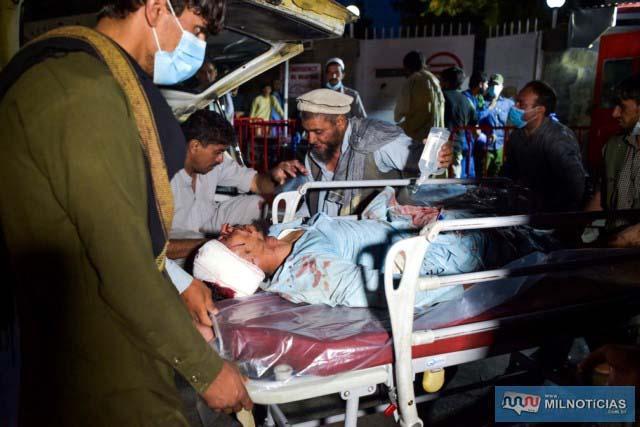 Equipe médica e hospitalar trazem um homem ferido em uma maca para tratamento após duas explosões no aeroporto de Cabul, nesta quinta (26) — Foto: Wakil Kohsar/AFP