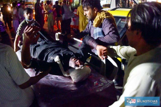 Médicos e funcionários de hospital atendem homem ferido em duas explosões do lado de fora do aeroporto de Cabul, no Afeganistão — Foto: Wakil Kohsar/AFP